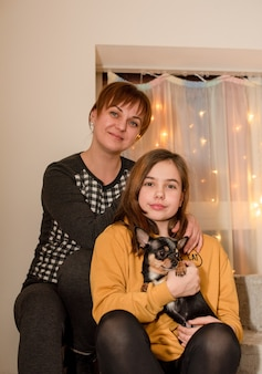 Adolescente, mãe e cachorrinho chihuahua. menina com a mãe em casa