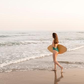Adolescente magro andando perto da costa com a prancha de surf na praia