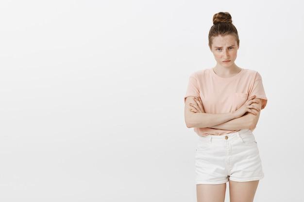 Adolescente mal-humorada ofendida parecendo zangada e cética