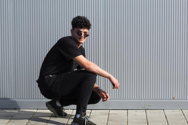Adolescente masculino de cócoras contra a parede cinza