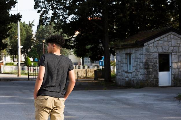 Adolescente masculino em pé e sonhar acordado na rua