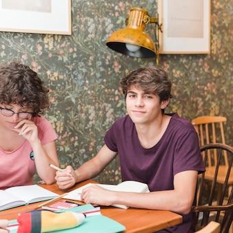 Adolescente masculino fazendo lição de casa com o amigo