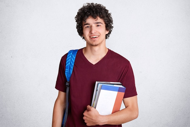 Adolescente masculino jovem positivo com sorriso encantador e agradável, detém livros, carrega saco, se prepara para as aulas na faculdade, gosta de estudar