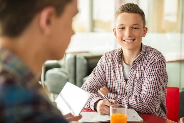 Adolescente masculino sentado no café com os amigos.