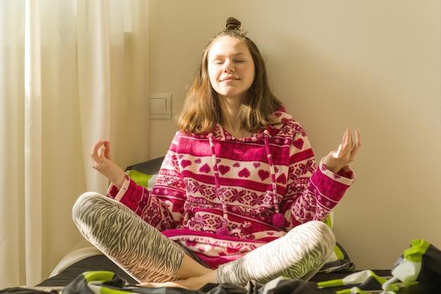 Adolescente meditando e sorrindo enquanto está sentado na pose de ioga