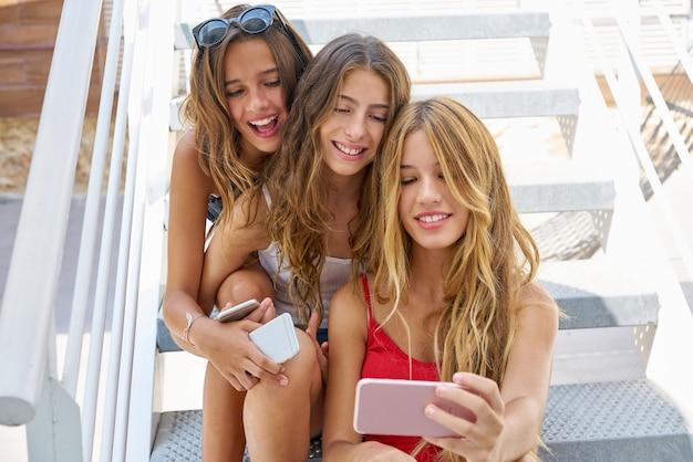 Adolescente melhores amigas meninas em uma fileira com smartphone