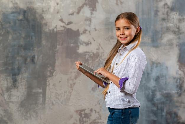 Adolescente menina bonita loira segurando o ipad nas mãos dela e olhando para a câmera
