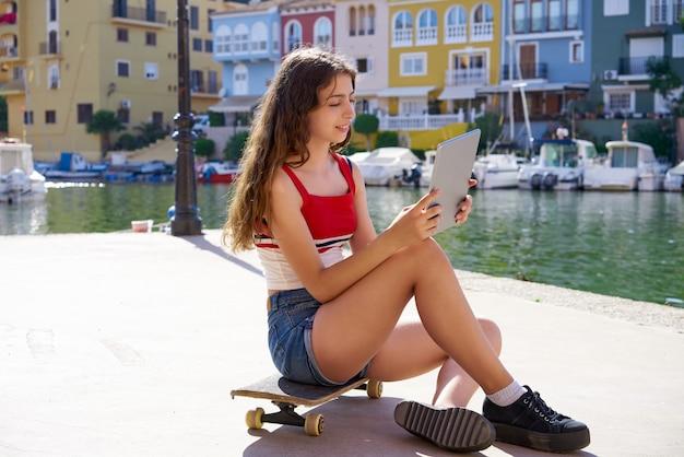 Adolescente menina com skate e tablet selfie