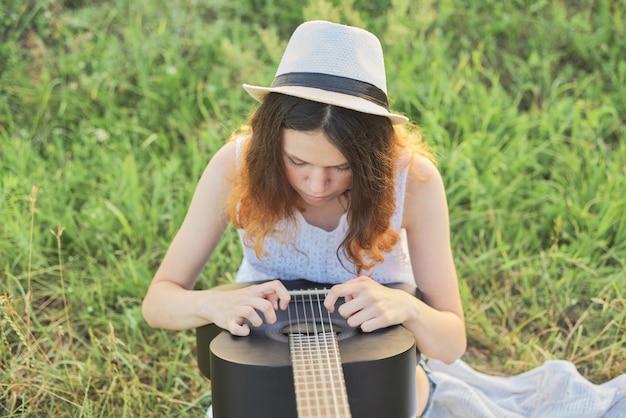Adolescente menina de chapéu tocando violão sentado na grama