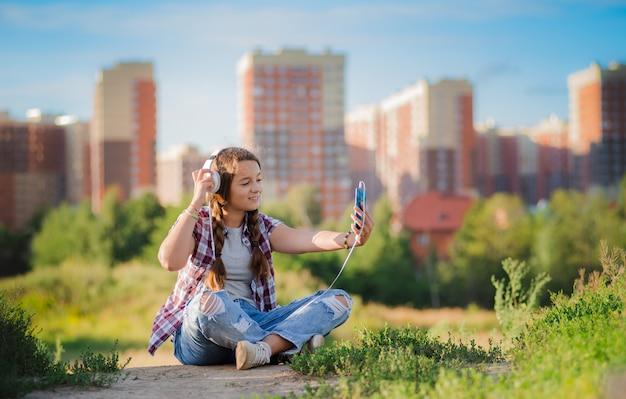 Adolescente menina de óculos senta a cidade do chão nos fones de ouvido do smartphone selfie