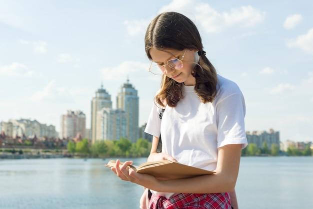 Adolescente, menina, desgastar, óculos, mochila, leitura, livro