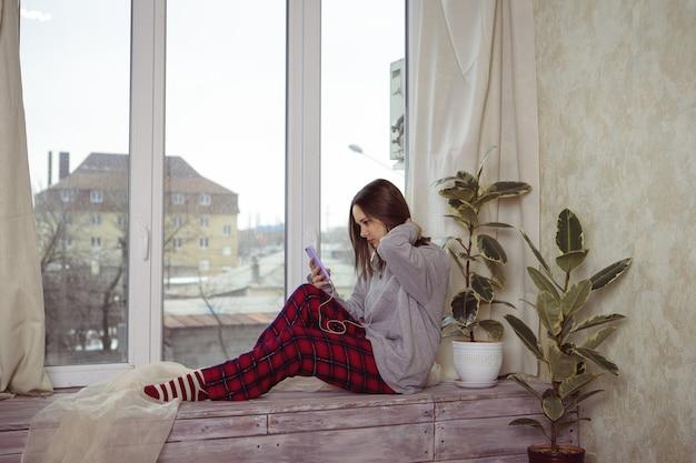 Adolescente menina senta-se na janela com o telefone na mão e ouve algo nos fones de ouvido. solidão. uma jovem mulher olha pela janela