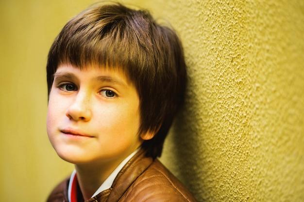 Adolescente menino posando contra um fundo de parede amarelo