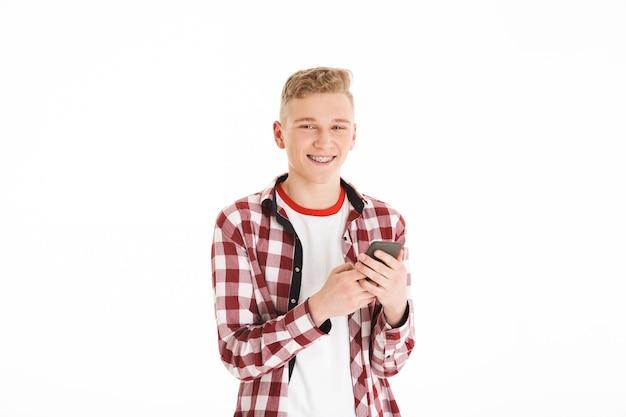 Adolescente moderno em t-shirt casual usando aparelho segurando o telefone celular e navegando ou digitando usando a internet, isolada sobre a parede branca