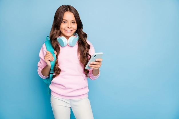 Adolescente moderno posando contra a parede azul