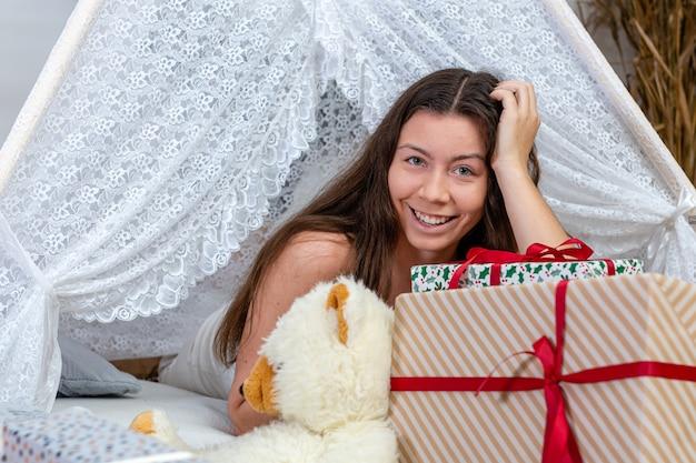 Adolescente morena deitada entre brinquedos e caixas de presente de natal