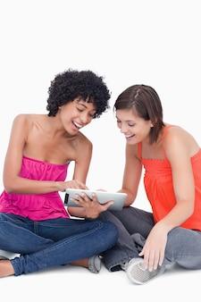 Adolescente mostrando uma aplicação engraçada em seu tablet pc para um amigo