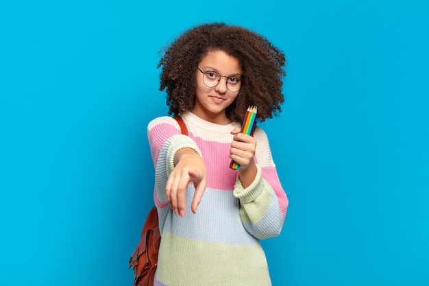 Adolescente muito afro apontando para a frente com um sorriso satisfeito, confiante e amigável, escolhendo você. conceito de estudante