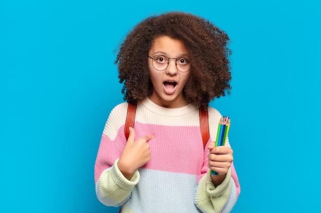 Adolescente muito afro parecendo chocado e surpreso com a boca aberta, apontando para si mesmo. conceito de estudante