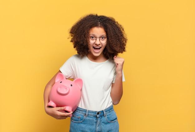 Adolescente muito afro parecendo feliz, espantado e surpreso, sorrindo e percebendo uma boa notícia incrível. conceito de economia