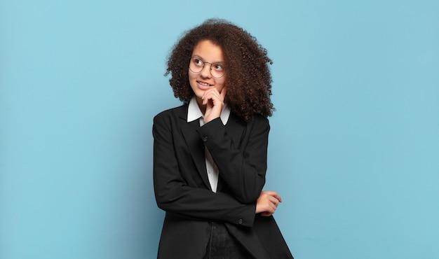 Adolescente muito afro sorrindo alegremente e sonhando acordado ou duvidando, olhando para o lado. conceito de negócio humorístico