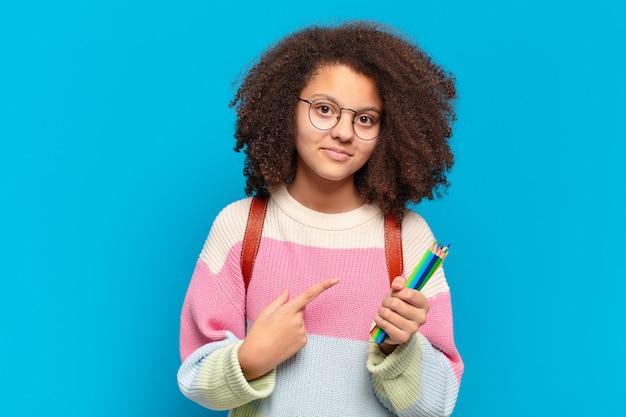 Adolescente muito afro sorrindo alegremente, sentindo-se feliz e apontando para o lado e para cima, mostrando o objeto no espaço da cópia. conceito de estudante