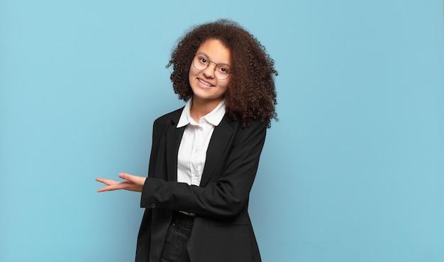 Adolescente muito afro, sorrindo alegremente, sentindo-se feliz e mostrando um conceito no espaço de cópia com a palma da mão. conceito de negócio humorístico