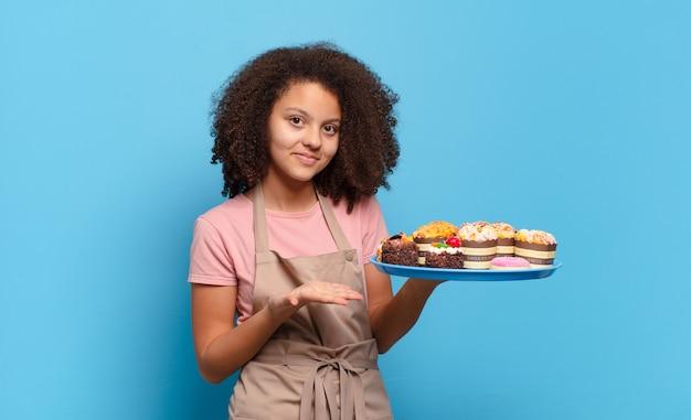 Adolescente muito afro sorrindo alegremente, sentindo-se feliz e mostrando um conceito no espaço de cópia com a palma da mão