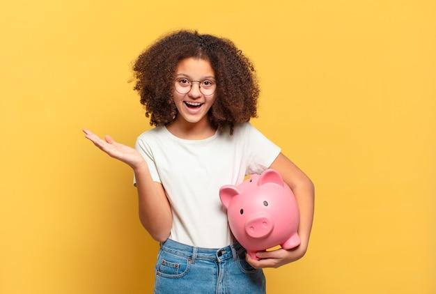 Adolescente muito afro sorrindo com confiança, apontando para o próprio sorriso largo, atitude positiva, relaxada e satisfeita. conceito de economia