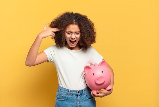 Adolescente muito afro sorrindo e parecendo amigável, mostrando o número dois ou o segundo com a mão para a frente, em contagem regressiva. conceito de economia