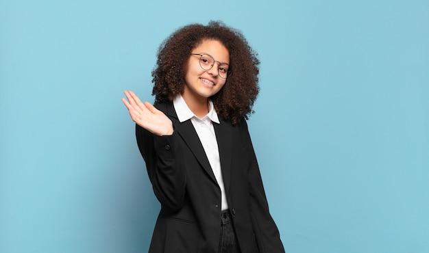 Adolescente muito afro sorrindo feliz e alegremente, acenando com a mão, dando as boas-vindas e cumprimentando você ou dizendo adeus. conceito de negócio humorístico