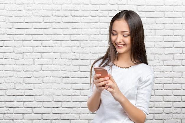 Adolescente muito feminino usando smartphone