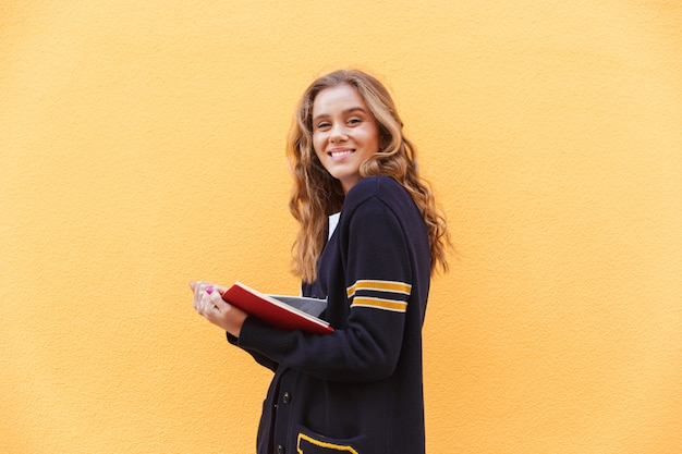 Adolescente muito sorridente, segurando o livro e olhando