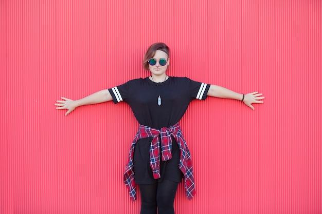 Adolescente mulher andrógina com os braços abertos em uma parede rosa