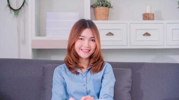 Adolescente, mulher asian, sentimento, feliz, sorrindo, e, olhando câmera, enquanto, relaxe, em, dela, sala de estar