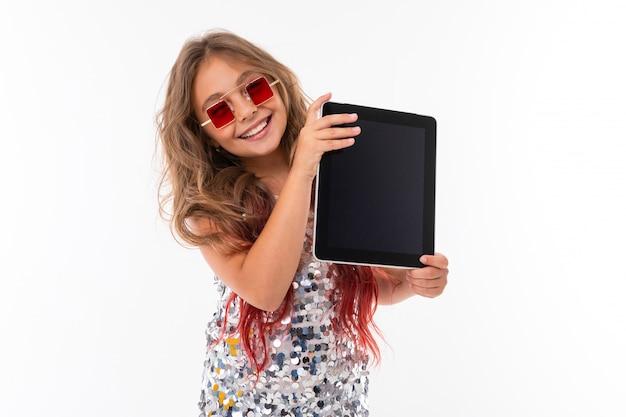 Adolescente mulher com longos cabelos loiros tingidos com dicas-de-rosa, em vestido claro brilhante, tênis preto e branco, óculos, em pé com fones de ouvido, segurando um tablet nas mãos