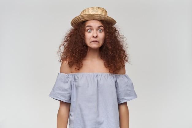 Adolescente, mulher confusa, com cabelo ruivo cacheado. usando blusa listrada de ombros largos e chapéu. conceito emocional. careta confusa. isolado sobre a parede branca
