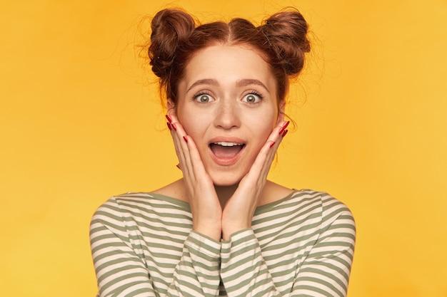 Adolescente, mulher de cabelo vermelho feliz olhando com dois pães. grita de surpresa e toca as bochechas, animada. usando um suéter listrado e assistindo isolado, close-up sobre a parede amarela