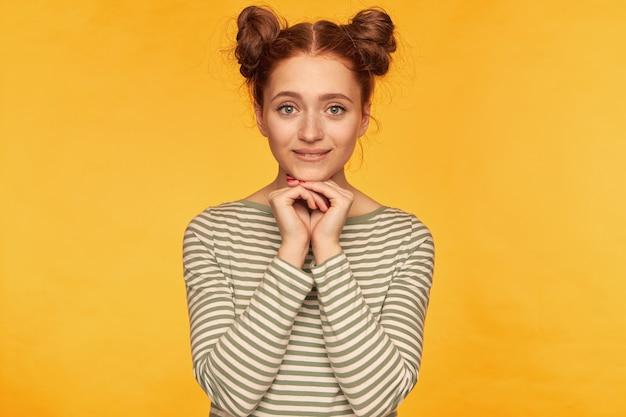 Adolescente, mulher de cabelo vermelho feliz olhando com dois pães. segurando as mãos cruzadas sob o queixo, em antecipação. usando um suéter listrado e assistindo isolado na parede amarela
