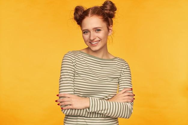Adolescente, mulher de cabelo vermelho feliz olhando com dois pães. vestindo um suéter listrado e mantém as mãos cruzadas sobre o peito. sorrindo assistindo isolado na parede amarela Foto gratuita