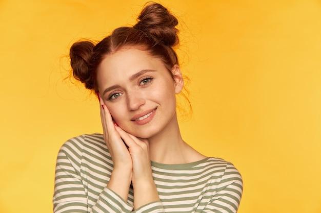 Adolescente, mulher de cabelo vermelho feliz olhando com dois pães. vestindo um suéter listrado e segurando as palmas das mãos perto de sua bochecha. assistindo isolado, close-up sobre a parede amarela