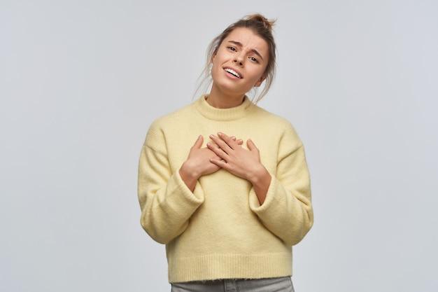 Adolescente, mulher encantadora com cabelo loiro reunido em um coque. vestindo um suéter amarelo. incline a cabeça e coloque as palmas das mãos no peito. ouça elogios. olhando para a câmera, isolada sobre uma parede branca