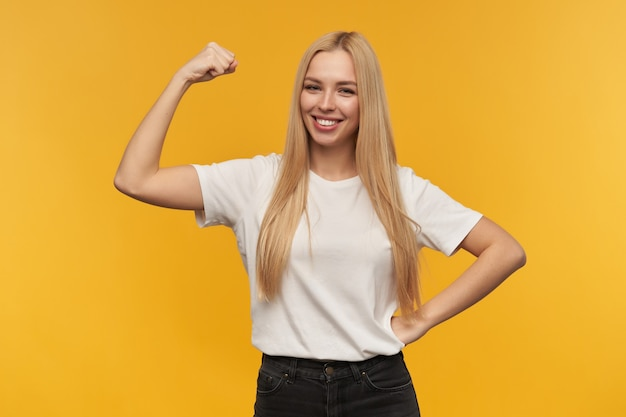 Adolescente, mulher feliz com cabelo comprido loiro. vestindo camiseta branca e jeans preto. mostra seus músculos olhando para a câmera, isolado sobre um fundo laranja
