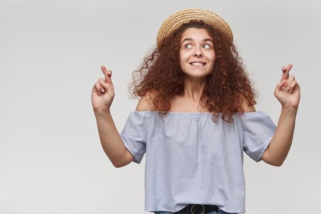 Adolescente, mulher feliz com cabelo ruivo cacheado. usando blusa listrada de ombros largos e chapéu. fazendo um pedido. observando à esquerda no espaço da cópia, isolado sobre a parede branca