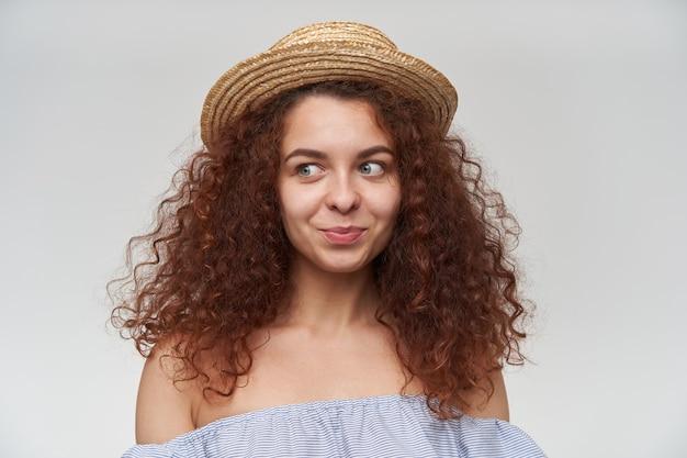 Adolescente, mulher feliz com cabelo ruivo cacheado. usando blusa listrada de ombros largos e chapéu. observando à esquerda no espaço da cópia, close, isolado sobre a parede laranja