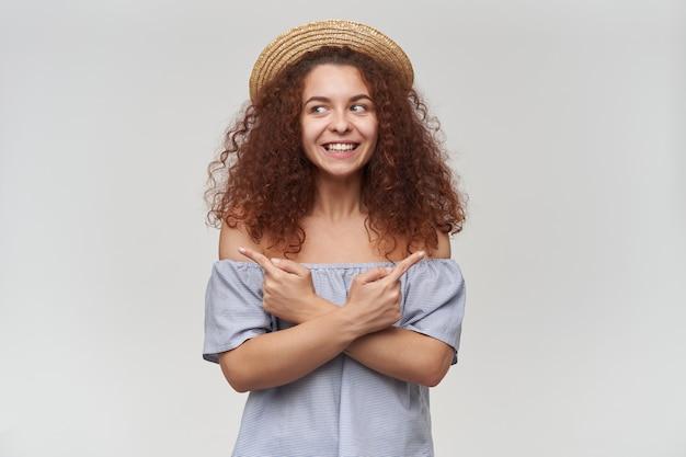 Adolescente, mulher feliz com cabelo ruivo cacheado. usando blusa listrada de ombros largos e chapéu. observando para a esquerda no espaço da cópia e apontando os dois lados, isolado sobre a parede branca