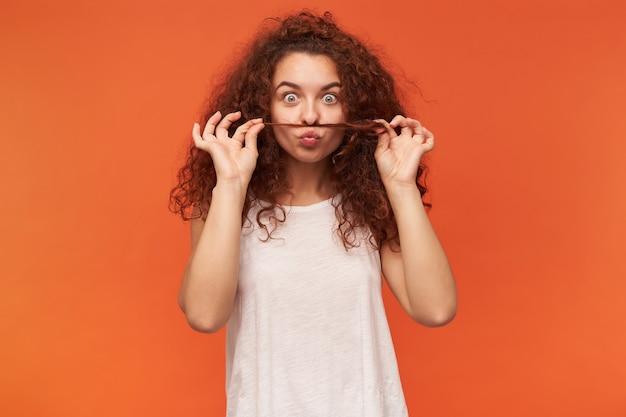 Adolescente, mulher feliz com cabelo ruivo cacheado. usando uma blusa branca sem ombros. brinque com uma mecha de cabelo, finja que é bigode. isolado sobre a parede laranja