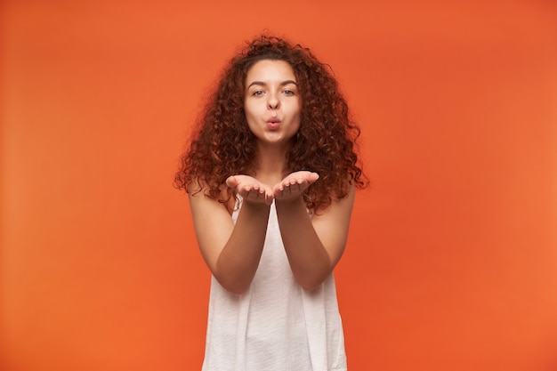 Adolescente, mulher feliz com cabelo ruivo cacheado. usando uma blusa branca sem ombros. enviando beijo no ar, soprando nas palmas das mãos. isolado sobre a parede laranja