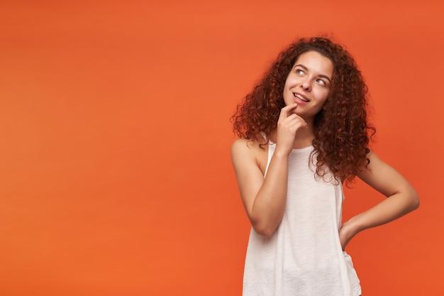 Adolescente, mulher feliz com cabelo ruivo cacheado. usando uma blusa branca sem ombros. tocando seu queixo e pensando. observando à esquerda no espaço da cópia, isolado sobre a parede laranja