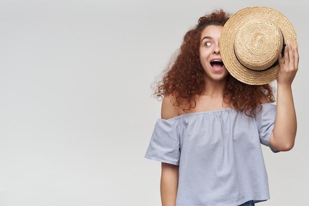 Adolescente, mulher feliz com cabelo ruivo cacheado. usando uma blusa listrada de ombros largos e cobrindo metade do rosto com um chapéu. observando à esquerda no espaço da cópia, isolado sobre a parede branca